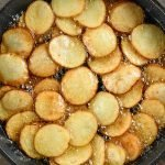 frying potatoes in pan with oil.