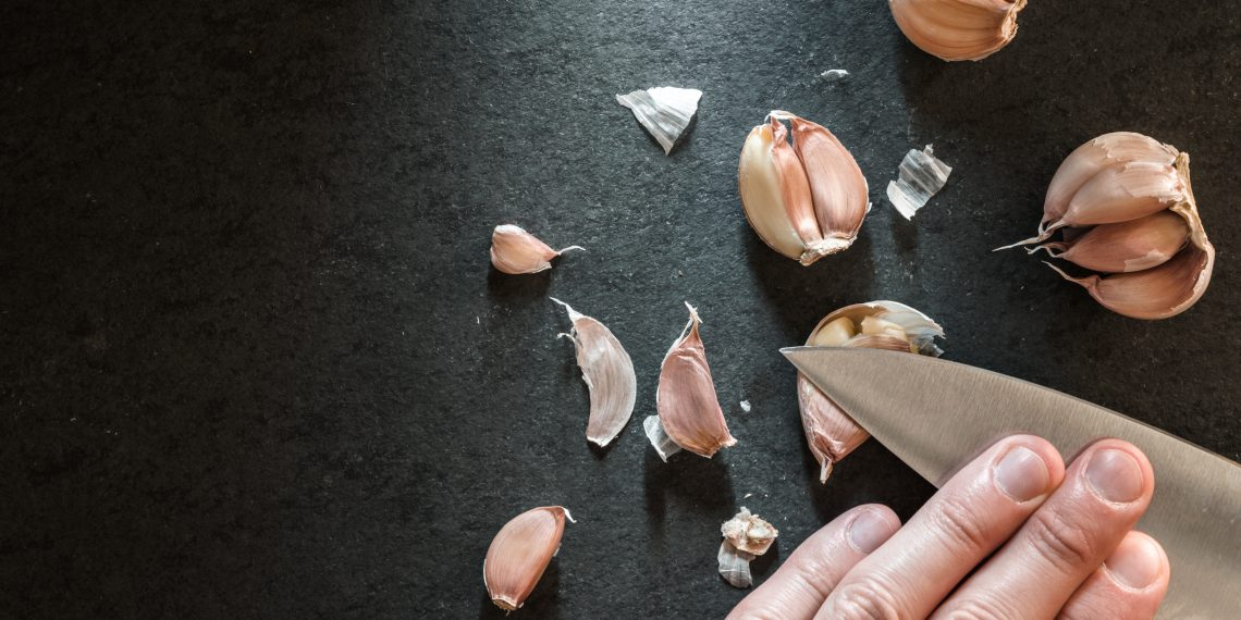 Peeling the garlic with a knife.