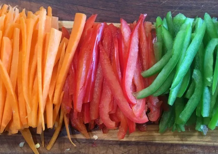 Finely julienned carrot, red bell pepper, and green bell pepper for quick cooking in a stir-fry